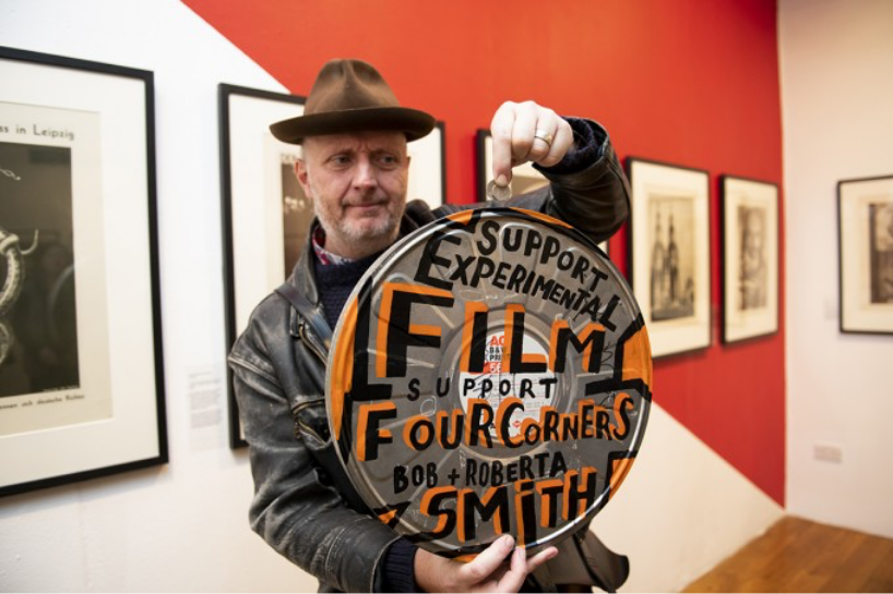 Photograph of the artist Bob and Roberta Smith holding a film canister with the words 'Support experimental film, support Four Corners' written on it.