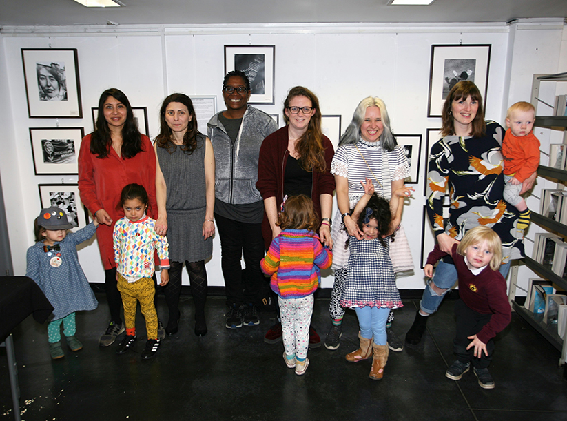 Six mums and six small children stand in front of a wall displaying framed black and white photographs.