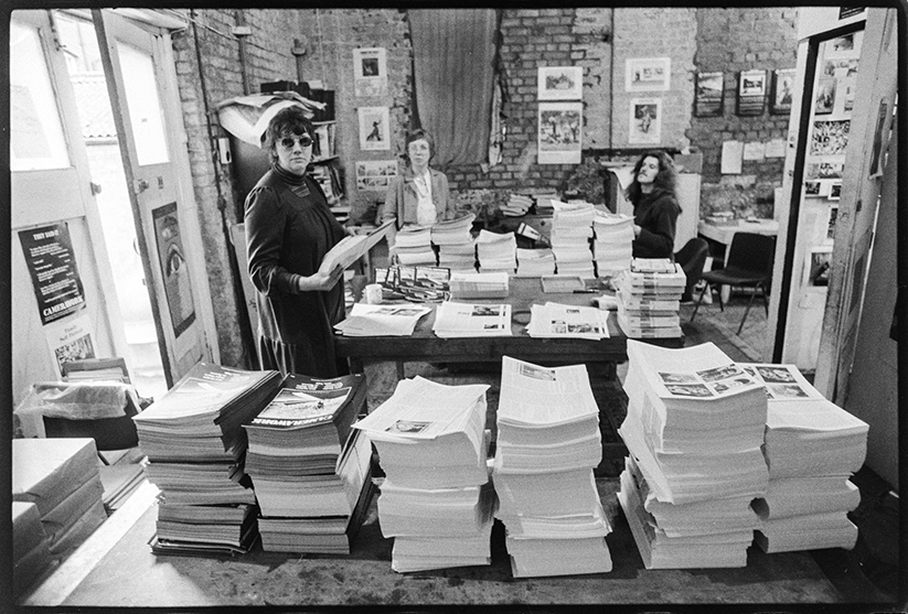 Black and white archive photograph of Jo Spence, Shirley Read and Ed Barber, standing behind tall stacks of Camerawork magazine.