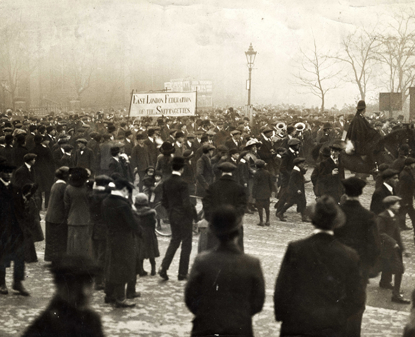 Black and white archive photograph of an East End Federation of Suffragettes march in Victoria Park. It it misty and the trees are bare. There is a mounted police officer to the right.