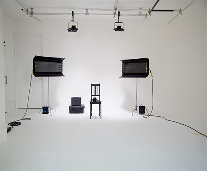 White infinity studio with two large black box lights, a black chair, and some wires and boxes.